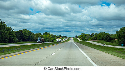 Long highway in the american countryside, blue cloudy sky background