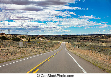 Long highway in the american countryside, blue sky