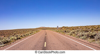 Long highway in the american countryside, clear blue sky