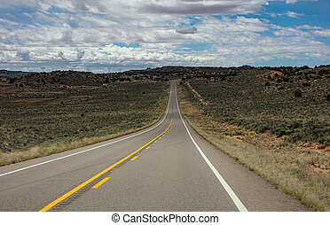 Long highway in the american countryside, cloudy blue sky