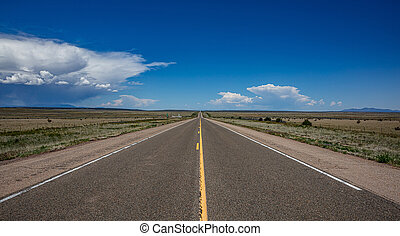 Long highway in the american desert, blue sky with clouds