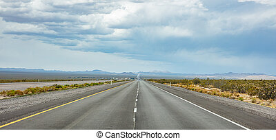 Long highway in the american desert, cloudy blue sky