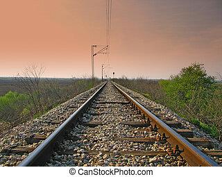 Straight train tracks with dark sky above