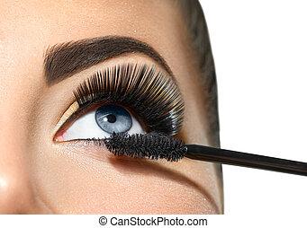 Long lashes closeup. Beautiful woman applying mascara on her...