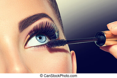 Long lashes closeup. Beautiful woman applying mascara on her eyes. Makeup