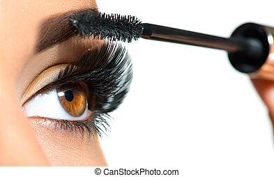 Long lashes closeup. Beautiful woman applying mascara on her eyes. Makeup