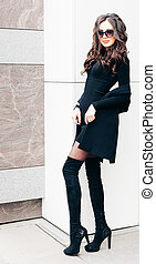 Long-legged beauty of a brunette in sunglasses posing A small black dress, high boots with high heels.