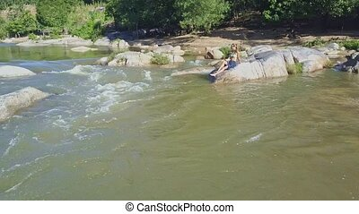Long Legged Girl Sits on Boulder and Watches River Rapids -...