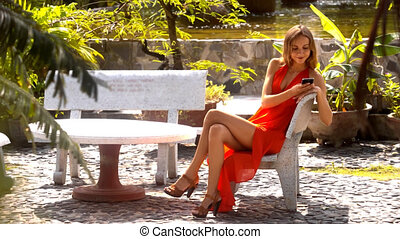 Long Legged Girl Sits with Phone in Pictorial Park - close...