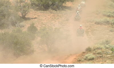 long line of ATV riders on dirt road