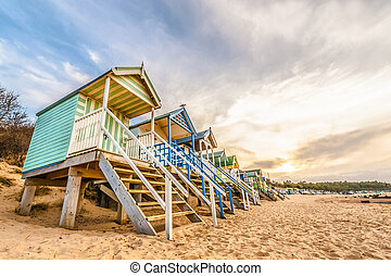 long line of colorful beach huts at sunset