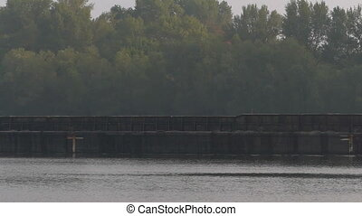Long Metal Barge Moves Along The Dnipro With Trees in the...