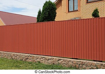 long metal red fence wall on a stone foundation