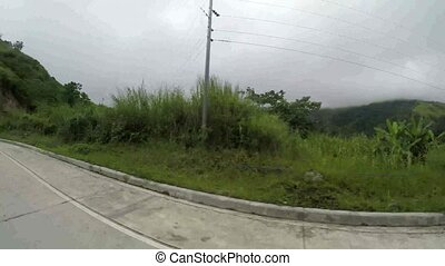 Long narrow concrete paved road at the side of mountainous...