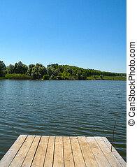 Long Old wooden pier and beautiful lake. Empty on small country lake. of summer. Place for text and fishing