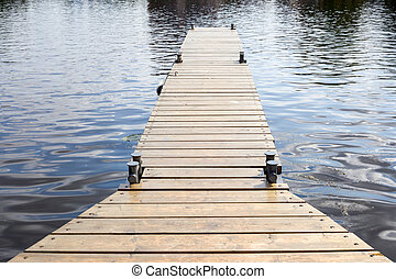 Long old wooden pier in water at summer time