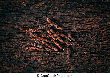 Long Pepper dry on wood background. Indian long pepper, ...