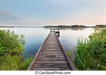 long pier on lake and blue sky