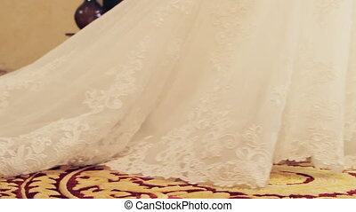 Long plume of the bride dress stretches the carpet. Wedding...