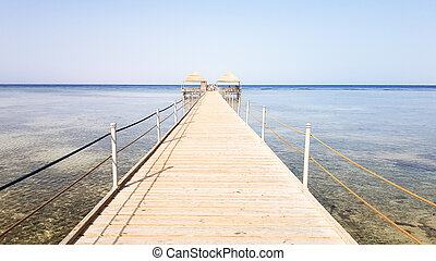 Long pontoon on the Red Sea in Egypt. Pontoon for descent into the water. Wooden bridge on the territory of the Amway Hotel in Sharm El Sheikh with metal fences and a rope over the sea with waves