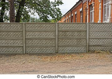 private concrete gray fence on a rural street in the grass
