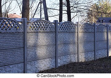 long private concrete gray fence on a rural street