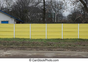 long private concrete yellow fence on a rural street