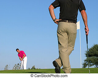 Long putt - Golfer watching his opponent take a long ...