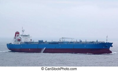 long red and blue tanker floating on waves in cloudy weather