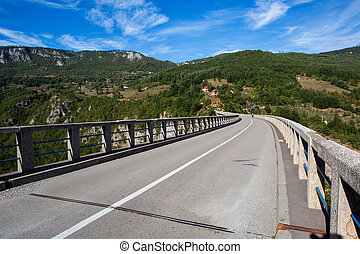 long road on the bridge in the mountains