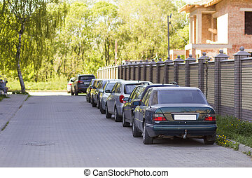 Long row of cars parked in quiet neighborhood on clean empty paved street along new stone fence on background of unfinished brick house and beautiful green trees on bright sunny summer or spring day.