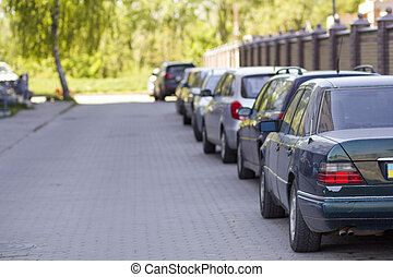 Long row of cars parked in quiet neighborhood on clean empty paved street along new stone fence on background of beautiful green trees on bright sunny summer or spring day.