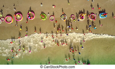 long row of plastic pools on beach kids play - aerial...