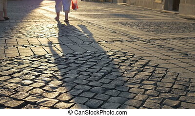 Long Shade on Cobblestone - Long shades of walking people in...