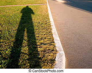 Long Shadow Of A Man Casting On Green Lawn At Sunset. Curved Curb And Sidewalk.