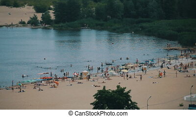 long shot of people on the beach on a sunny summer day -...