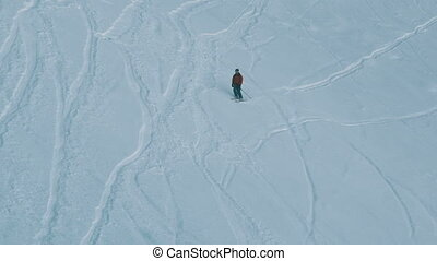 Long shot of the skier descends on the extreme snow-covered...