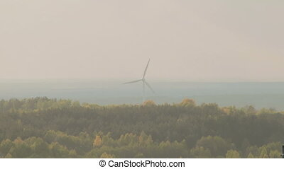 Long shot on lonely electric windmill in green forest,...