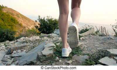 Long Slim Beautiful Female Legs In Sneakers Walking On The Rocky Road And Stops At The Top of The Mountain