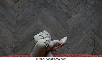 Long slim tattoed legs crossed in beige stylish heels....