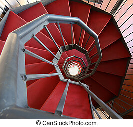 long spiral staircase with red carpet