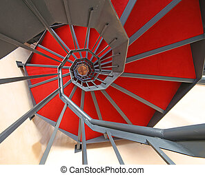 long spiral staircase with red carpet in a building