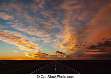 Long straight highway on the pampas in Patagonia with spectactular sunrise and clouds.