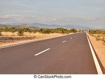 Long straight road with mountainous view in Croatia