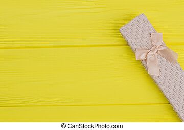 Long stylish gift box on yellow wood.