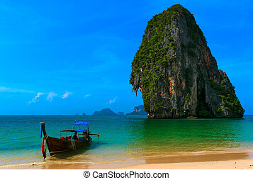 Long tail boat in tropical beach with cliff , blue sky and clear sea water. Travel background.