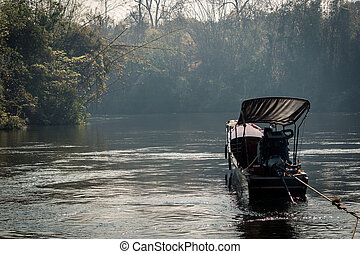 Long tail boat on a river in the jungle.