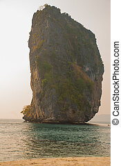 Long tail boat on tropical beach with limestone rock. Sunset, island Taming. Krabi, Thailand.