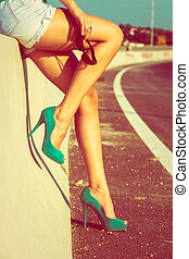 woman tan legs in high heel green shoes outdoor shot summer day