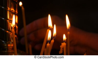 Long thin wax candles burn with a flame in an Orthodox church, memorial rituals for Christians. a woman's hand puts a candle in a special candlestick